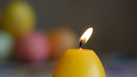 Candles made in shape of easter egg. Burning candles. Yellow candles Live Action