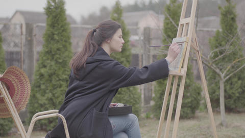 Skillful artist paints on the canvas in the backyard. Beautiful enthusiastic Live Action