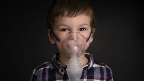 Footage young boy inhaling through inhaler mask Footage