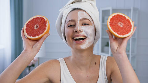 Portrait shot of handsome young woman posing with two half of grapefruit on eyes Footage