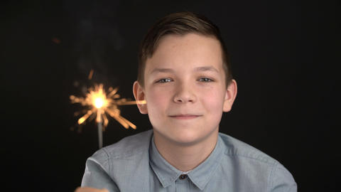 Happy adorable boy holding a sparkler Live Action