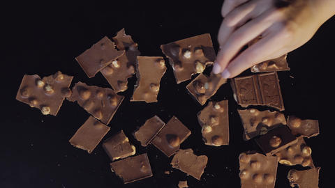 Woman hand puts piece of chocolate bar to a bunch of chocolate pieces Live Action