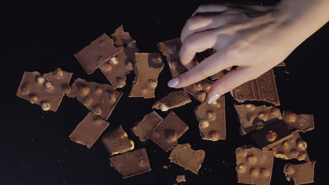 Woman hand takes piece of chocolate from a bunch of chocolate pieces Live Action