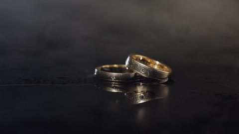 Wedding rings on dark water surface shining with light. Close up macro Footage