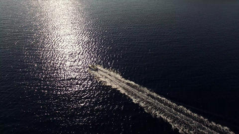 Aerial - Motor boat ride. Sunlight reflection in the sea Live Action