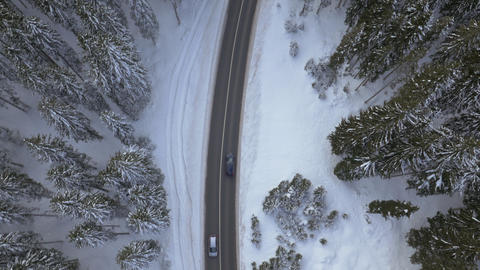 Aerial - Rotating above the road among snowy forest with driving cars Footage