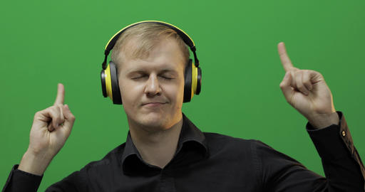 Guy listens to music in wireless yellow headphones and dances. Green screen Footage
