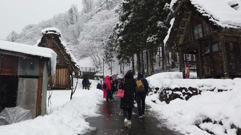 Tourists walking at historic village during snowing in winter season GIF
