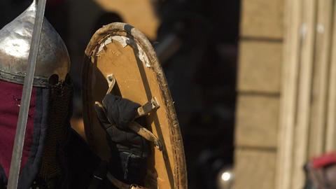 Warrior in a worn armor dodging rival strikes Archivo