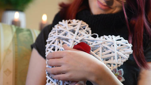 Valentine Gift. Young Girl holding white wooden heart with rose petals Footage
