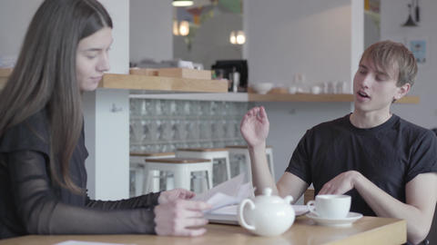 Young successful guy and girl communicate sitting at the table in a cozy cafe or Footage