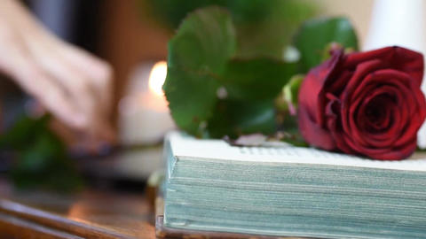 close up picking up a red rose from table with book and candles Footage
