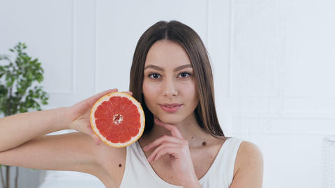 Portrait shot of handsome young woman posing with half of grapefruit Live Action