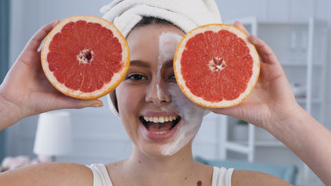Attractive smiling woman posing with two half of grapefruit on eyes with mask on Live Action