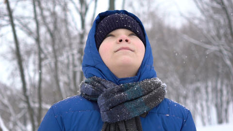 portrait young teenage boy enjoying snow in the winter forest, snow falls Live Action