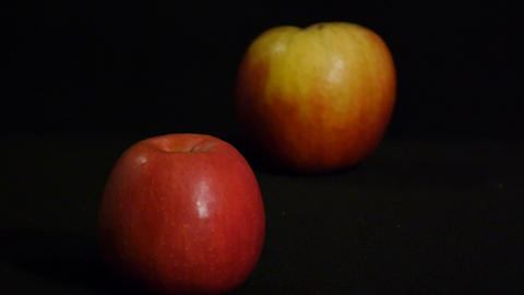 Still life of two red apples isolated on a black background. Close up Footage