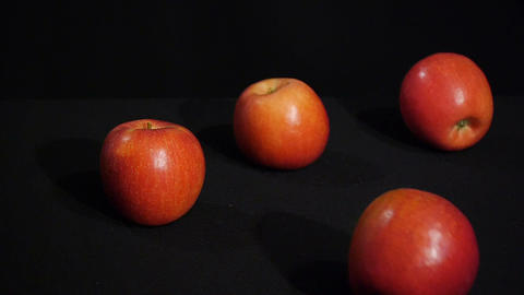 Beautiful red apples rolling on a black background. Juicy fruits Footage
