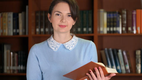 portrait of smiling beautiful pretty woman with book in library office bookshelf Footage