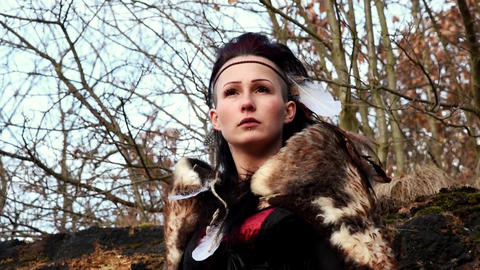 Beautyful viking woman seated on a rock in autumn nature landscape Live Action