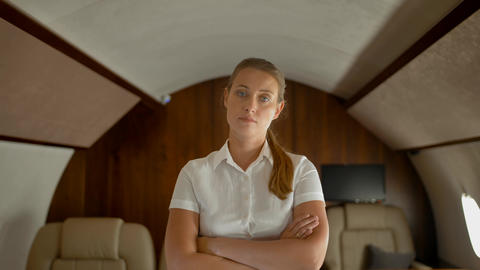 Confident businesswoman inside of private jet standing, seriously looking at Archivo
