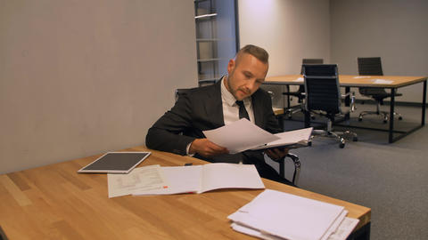 Confident businessman working with documents in night office indoor Footage