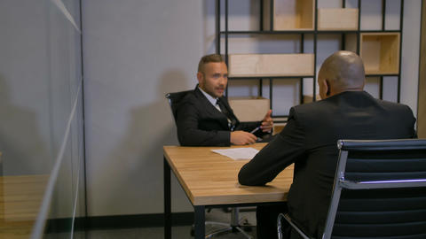 Two confident african american and caucasian bussines people in boardroom Footage
