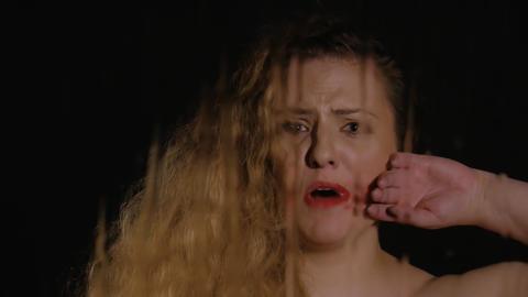 Cute woman wipes lipstick in rainy window Footage