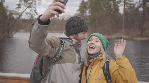 Young couple of travelers taking selfie while standing on a bridge against the Footage