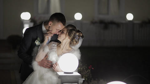 Groom with bride in cold evening on a bridge covered with many lanterns. Autumn Footage