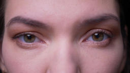 Close-up eye-portrait of calm brunette businesswoman watching seriously into Footage