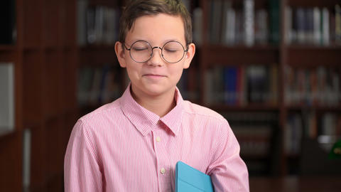 portrait shot of the cute schoolboy with tablet and standing near the bookshelf Live Action