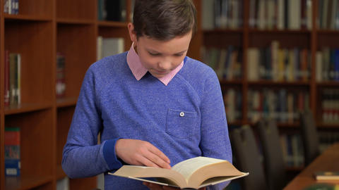 portrait shot of the cute schoolboy and standing near the bookshelf in the Live Action