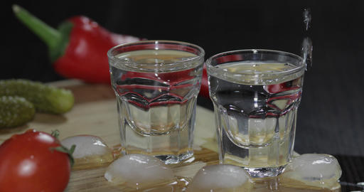 Pour vodka from a bottle into shot glasses. Man takes a glass with vodka Footage