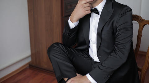 Handsome man sitting on a chair in black suit with bow tie. Businessman Live Action
