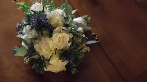 Wedding rings lie near beautiful wedding bouquet on the wooden table Archivo