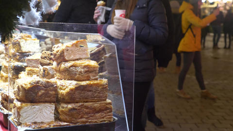 Food stall at christmas market with people passing by Footage