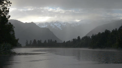 The rain and bright rays of morning sun over the Lake Matheson Footage