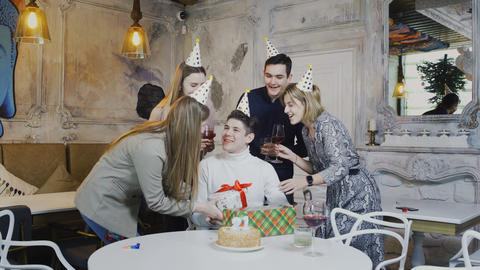 Smiling friends giving presents to birthday man, having party time at the Live Action