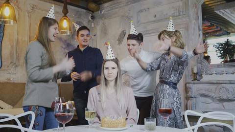 Sad birthday girl is sitting at the table while friends congratulate her Footage