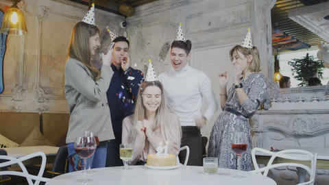 Excited pretty woman blowing birthday candles while dearest friends throwing Footage