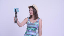 Happy young beautiful tourist woman vlogging and showing phone Archivo