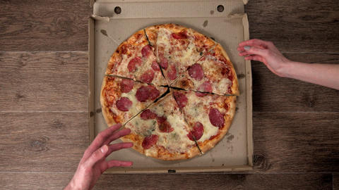 Delivery and opening a pizza box, different hands take pieces, stop motion Footage