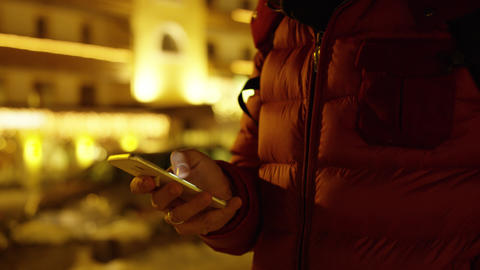 Unknown man in red jacket uses his smartphone. Winter evening. Shot on Red Live Action