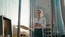 Business Woman is Using Phone App and Walking by Office Building with Sun Glare Archivo