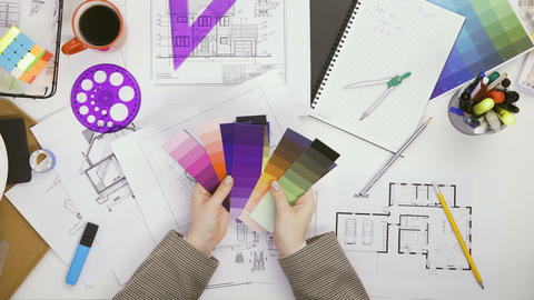 Over top view of architect woman choosing colors from color pallet Live Action