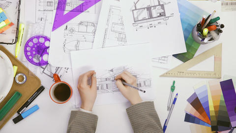 Top view on female hands of architect drawing a building plan and poured coffee ビデオ
