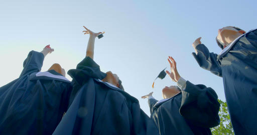 graduation students in bachelor gowns throwing mortar boards up in the air Footage