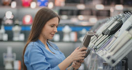 Young beautiful girl in blue shirt chooses blender in appliances store Footage