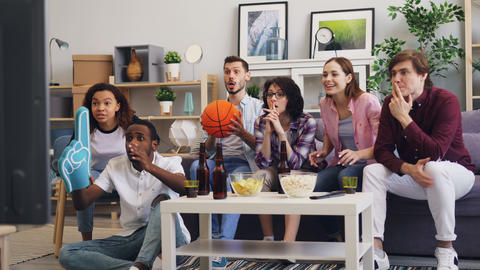 Basketball fans watching sports game on TV at home supporting favorite team Live Action