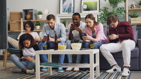 Multiracial group of friends using smartphones touching screen on sofa at home Footage